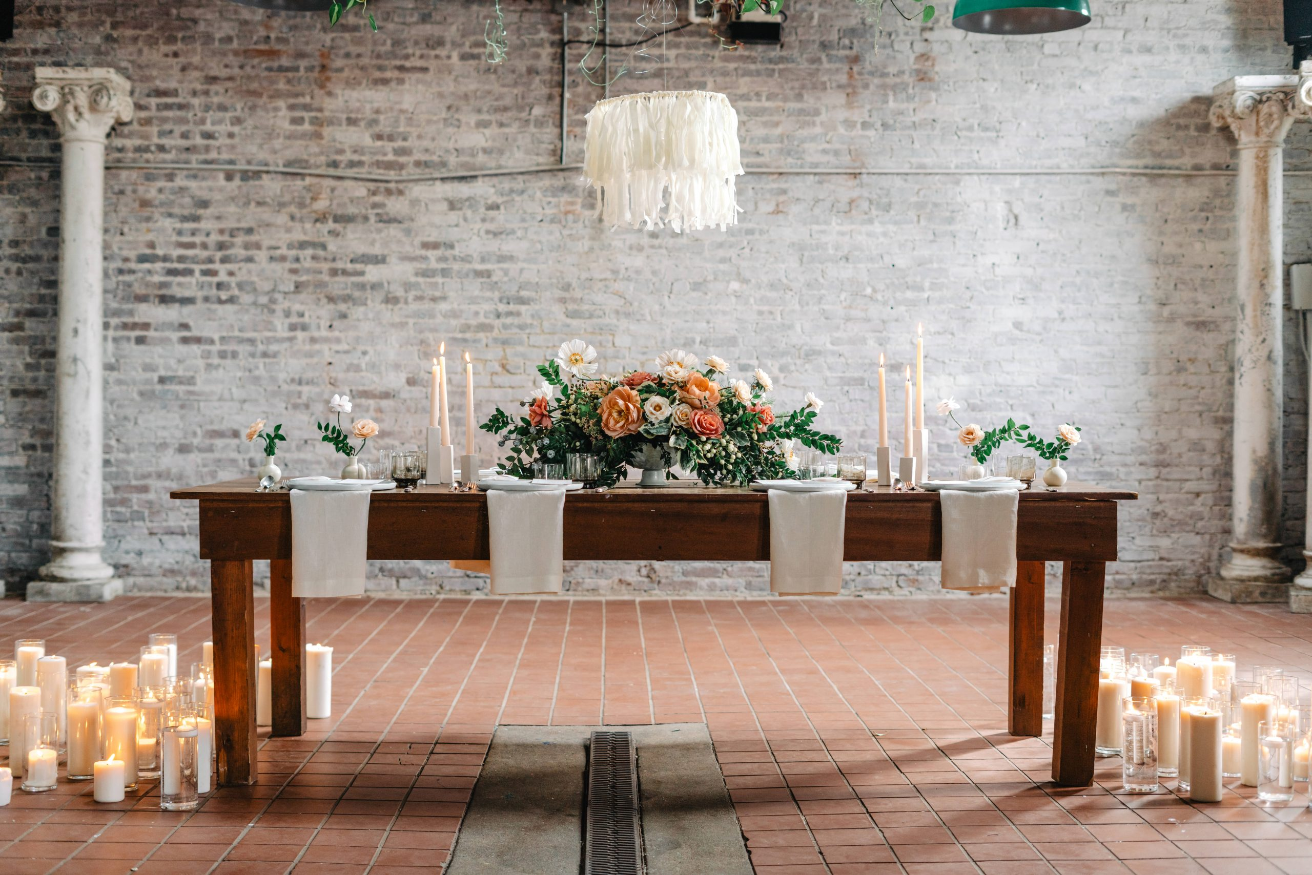 rustic table with flowers and candles in a warehouse