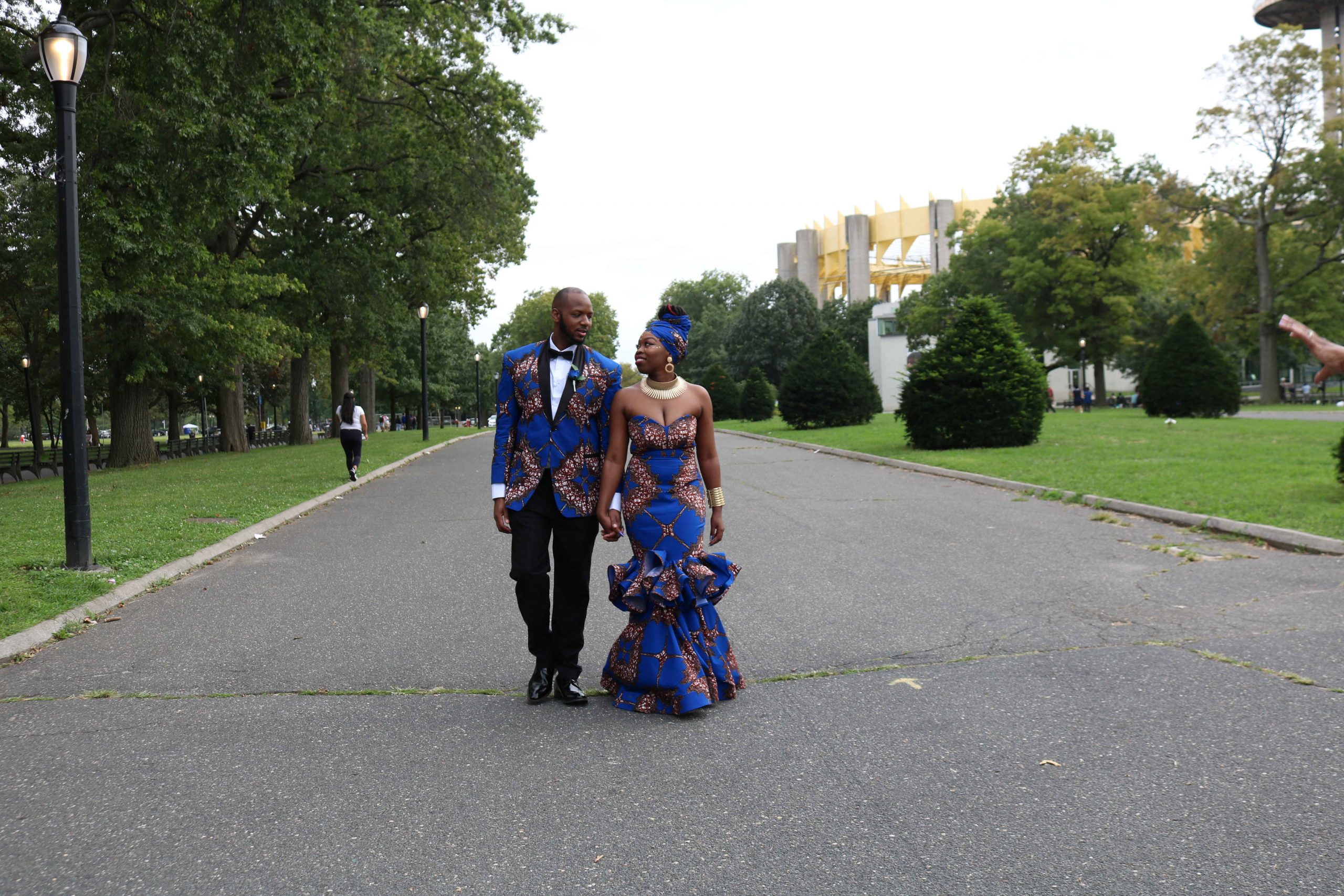 a bride and groom dressed in royal blue at Flushing Meadows Park
